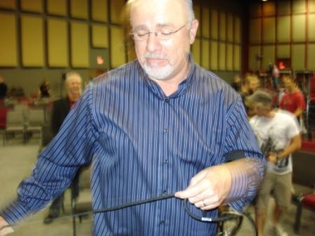 "Dave Ramsey going ""Office Space"" on a microphone.  You'll have to watch the event to understand this picture."